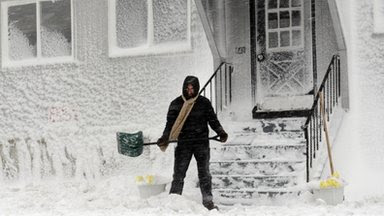 A man sweeps snow from the front of his house in Winthrop, Massachusetts, 9 February