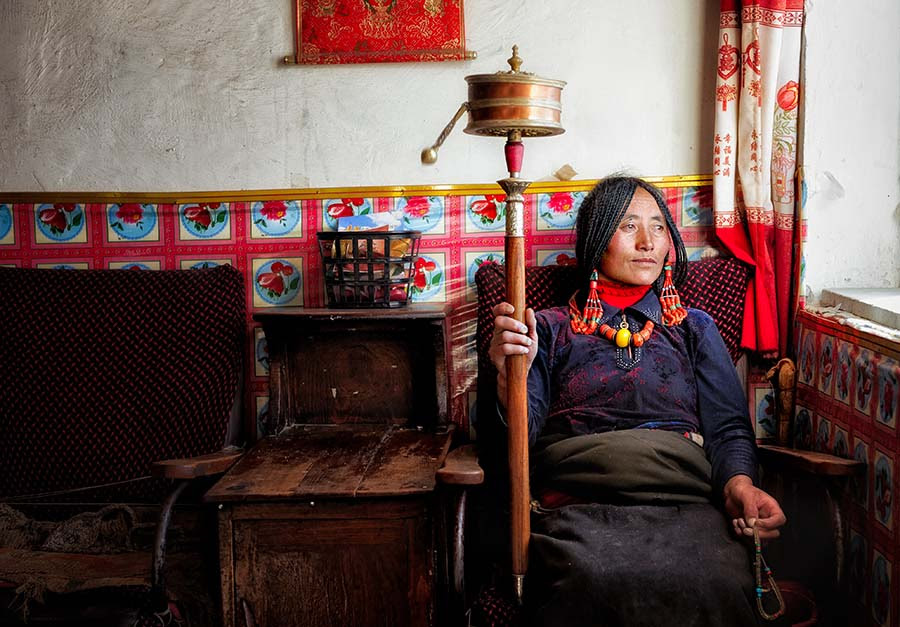 Tibetan woman deep into her prayers. Tibetan plateau