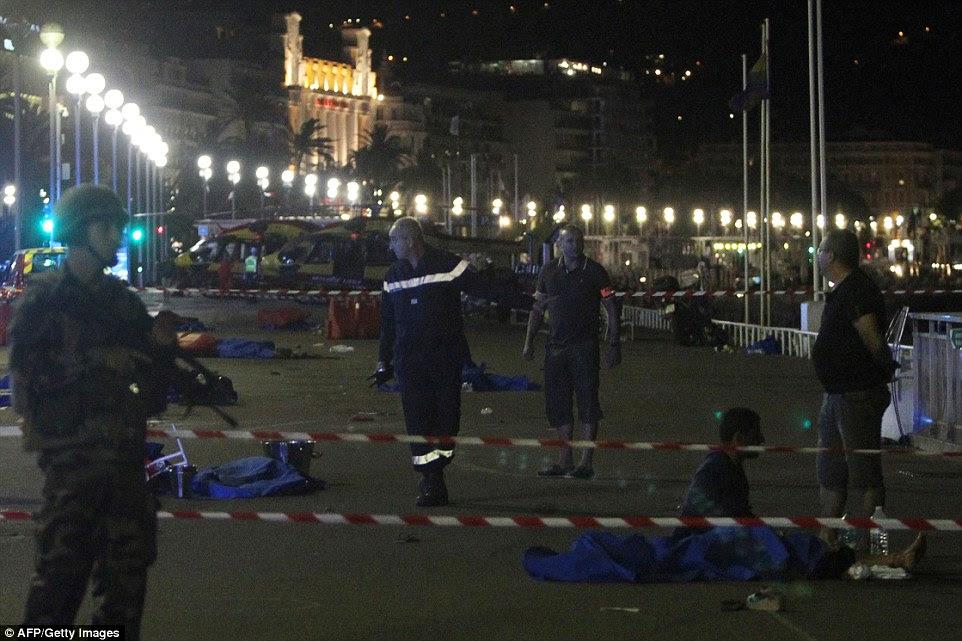 Soldados garantiu a cena enquanto equipes de emergência tratados os feridos e controlados com os mortos no massacre de ontem