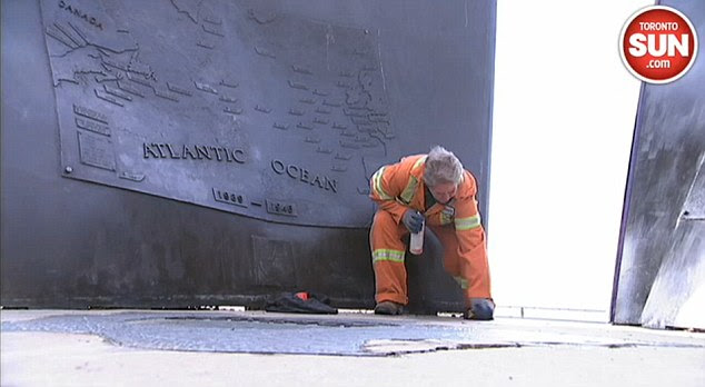 Clean up: Council workers inToronto scrub jihadist graffiti off a war memorial in Coronation Park