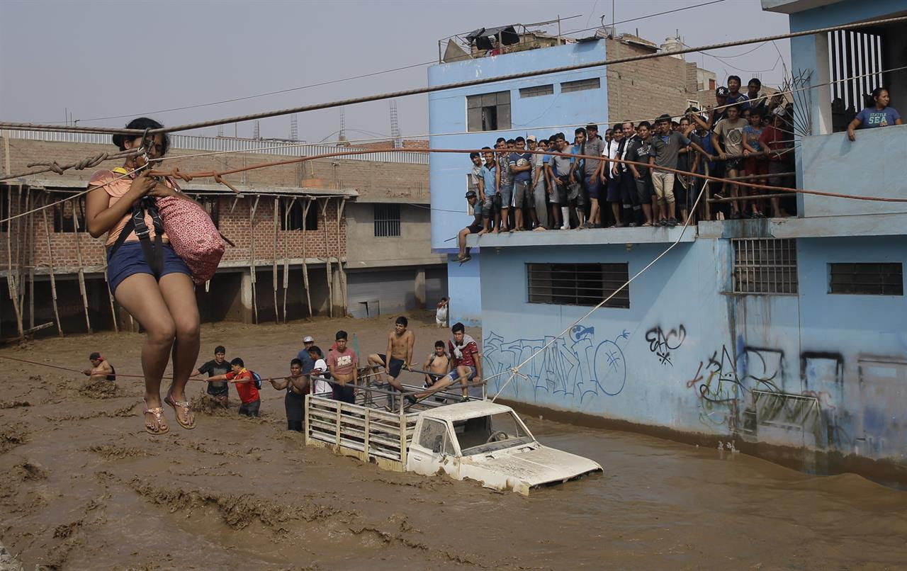 A woman is pulled to safety in a zipline harness in Lima, Peru, Friday, March 17, 2017. Intense rains and mudslides over the past three days have wrought havoc around the Andean nation and caught residents in Lima, a desert city of 10 million where it almost never rains, by surprise.