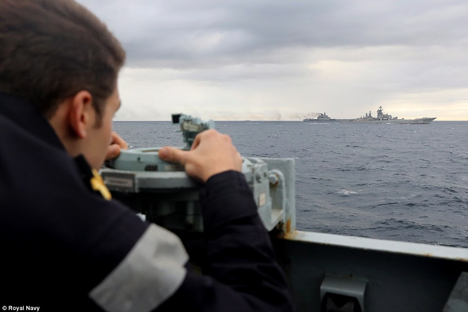 A Royal Navy seaman onboard the HMS Richmond keeps watch on the  Russian carrier fleet as it conducts training flight operations off the coast of the Shetland Islands