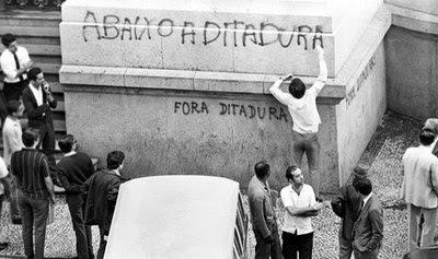 Foto em preto e branco mostra manifestantes escrevendo em um muro a frase 'Abaixo a Ditadura'