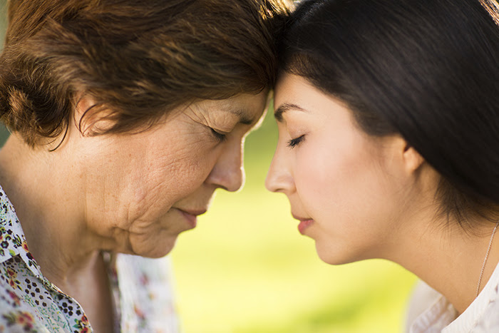 Asian mother and daughter with foreheads touching