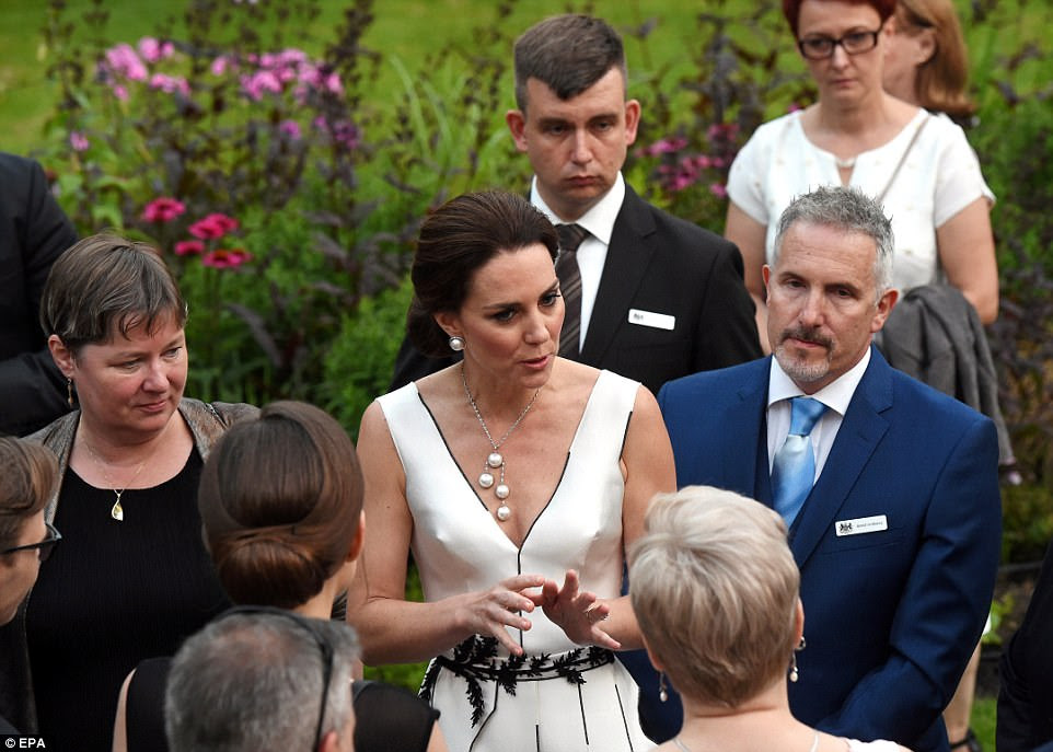 The Duchess appeared to have raised a smile among her hosts as she chats to guests at the 'wonderful' party. Their visit to Poland and Germany this week - accompanied by Charlotte and George - is seen by many as a Brexit charm offensive