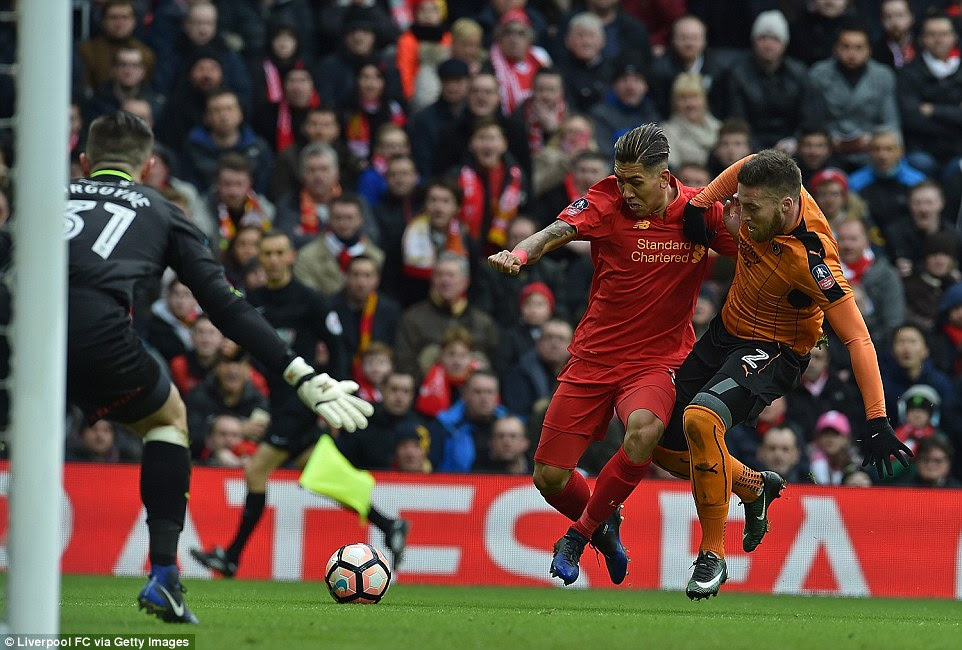 Liverpool forward Roberto Firmino grapples with Wolves' Matt Doherty as he ploughs into the penalty area