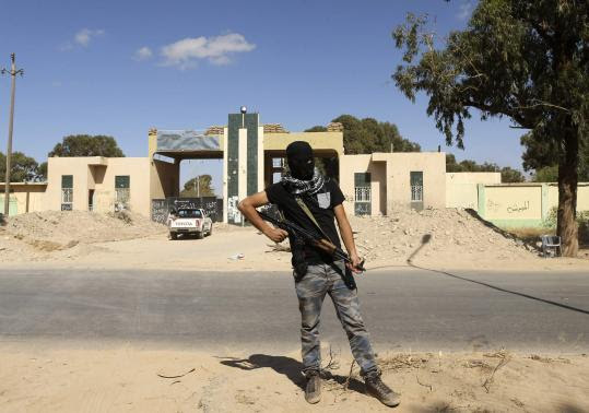 http://s1.ibtimes.com/sites/www.ibtimes.com/files/styles/v2_article_large/public/2014/05/16/militia-stands-guard-front-entrance-february-17-militia-camp-after-libyan-irregular-forces.jpg?itok=vxmR22Q8