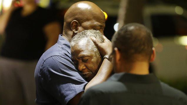 Des hommes s'enlacent après une fusillade dans une église à Charleston.