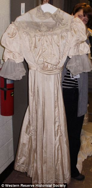 1900's gown of ivory silk with a high lace collar