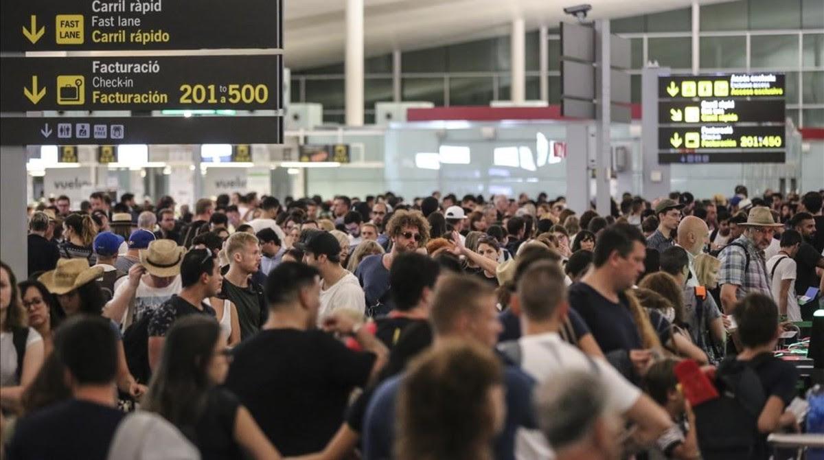 Aglomeración de viajeros en los controles de seguridad de la T-1 del aeropuerto de El Prat.