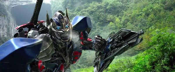 Optimus Prime is ready to confront a charging Grimlock (off-screen) in TRANSFORMERS: AGE OF EXTINCTION.