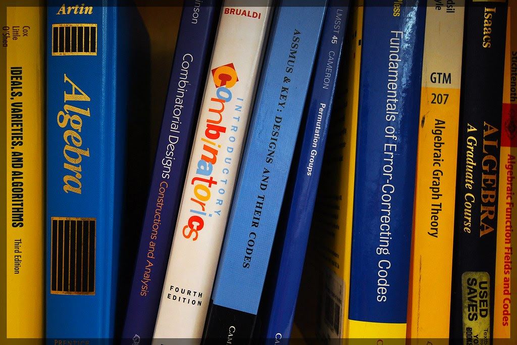 Colorful math books, lined up on a shelf.