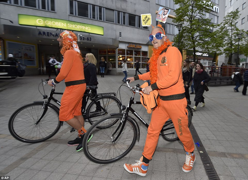 Fans from the Netherlands arrive dressed with bicycles and orange tracksuit bottoms and mirrored sunglasses