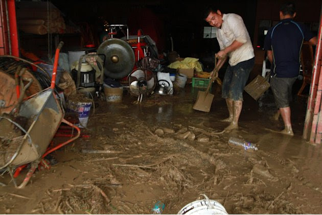 Taiwanese people scrape the mud off their house following flood and landslides triggered by typhoon Nanmadol in Laiyi, Pingtung County, Southern Taiwan, Monday, Aug. 29, 2011. Nanmadol slammed into Ta
