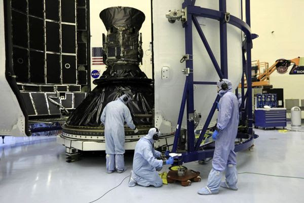 Engineers prepare to encapsulate NASA's TESS satellite with the payload fairing for SpaceX's Falcon 9 rocket at Kennedy Space Center in Florida...on April 9, 2018.