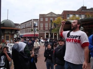 John Murphy, 24, of Falmouth, speaks to people in Harvard Square while wearing a shirt he made back at the Sign Tent at the Occupy Boston campground. (Blast Staff photo/John Stephen Dwyer)
