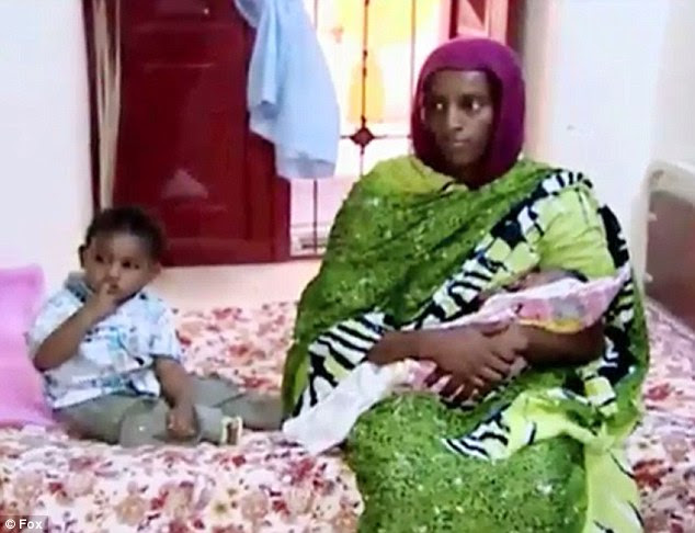 Meriam Ibrahim, 27, was pregnant with her second child when she was sentenced to hang for apostasy  under Sharia law. Above, she is pictured holding her newborn daughter Maya while sat next to her toddler son Martin