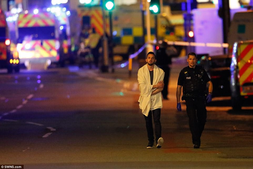 A man wearing a white towel walks next to a police officer. Concertgoers affected by the suspected terror attack  have been offered shelter by locals