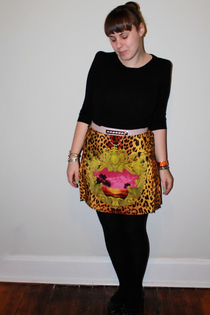 Versace skirt outfit: chain fastening belt, shoulder-pad sweater, black wool tights, stacked bracelets