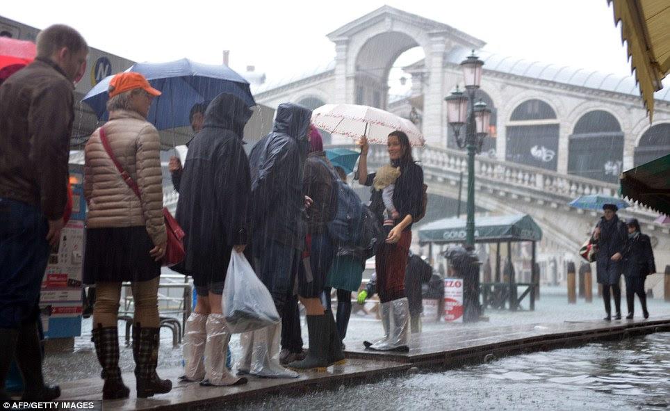 Tourists walk on footbridges near the Rialto bridge as heavy rain puts a dampener on their tour of the city