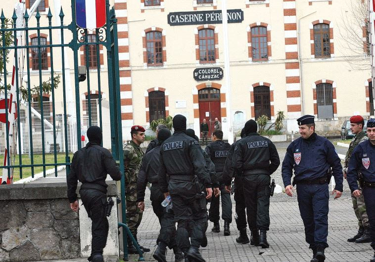MASKED FRENCH special unit policemen arrive at Perignon barracks after tracking down a terrorist in
