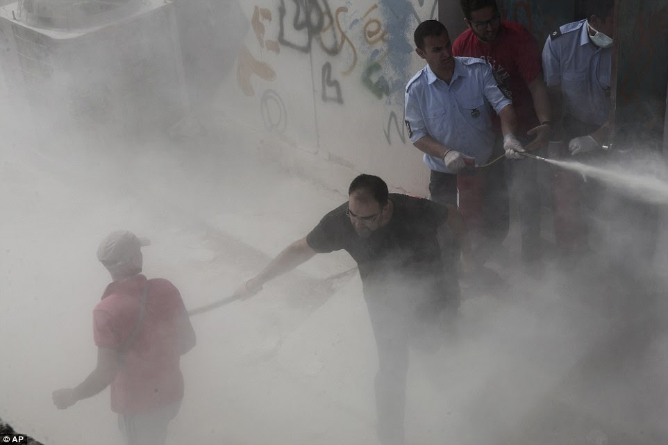 A policeman in plain clothes hits a migrant, as another sprays a fire extinguisher in an attempt to disperse hundreds of migrants