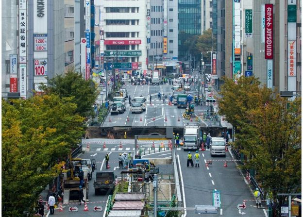 A huge sinkhole on a main street, viewed from a distance, near Hakata station in Fukuoka, Japan, 8 November 2016