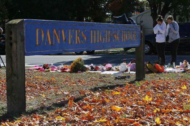 Students look over a makeshift memorial for teacher Colleen Ritzer outside the high school where she taught in Danvers, Massachusetts