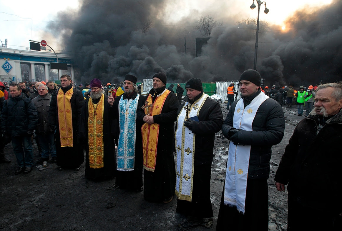 Priests of different faiths pray a protests during clashes with police in central Kiev (AP Photo/Sergei Chuzavkov)