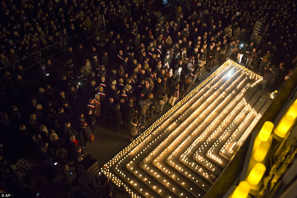 People gather near candles lit to commemorate the victims of the deadly attack on the Charlie Hebdo offices, in Lyon, central France