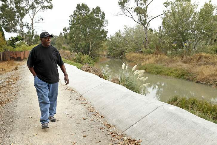 Curtis Sims wlks on the new levy built near a creek behind his home in East Palo Alto, Calif., on Thursday, October 15, 2015. Sims' home was flooded during the 1997-98 El Nino.