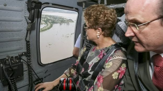 Brazil's President Dilma Rousseff (left) looks out of a plane window during a flight over flooded areas. Photo: 26 December 2015
