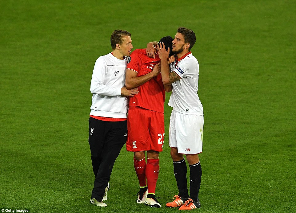 Can (centre) hides his face as he is consoled by Liverpool team-mate Lucas Leiva (left) and Sevilla's Carrico