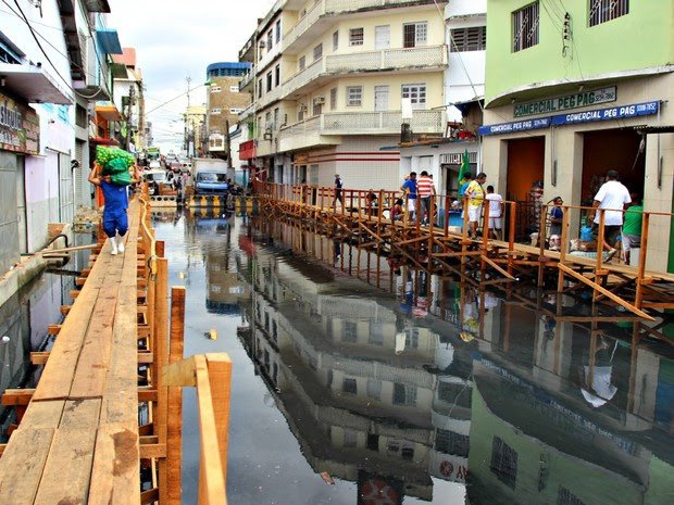 Carregadores precisam se equilibrar com mercadorias nas passarelas de madeira instaladas pela Defesa Civil (Foto: Adneison Severiano/G1 AM)
