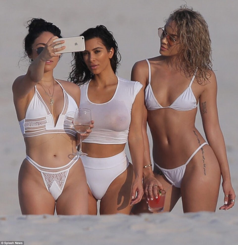 Sheerly delightful: Kim Kardashian gave a good look at her chest in this wet top as she posed for selfies with two female pals on the beach in Punta Mita, Mexico, on Friday
