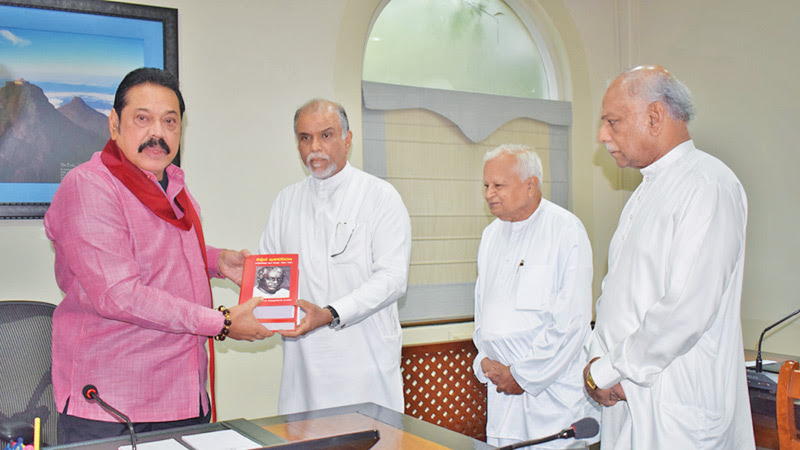 Chairman of the Philip Gunawardena Commemorative Society, Geethanjana Gunawardena presents the books to Prime Minister Mahinda Rajapaksa, at Temple Trees on Monday. Also present are Foreign Minister Dinesh Gunawardena and publisher S. Godage.