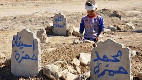 Autumn 2013: Ali Hamza, 8, sits at the graves of his brother, Mohammed, and sister Asinat