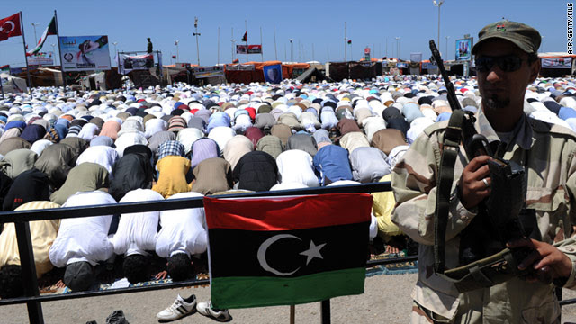 A Libyan rebel stands guard as Muslims perform a mass Friday noon prayer in the rebel stronghold of Benghazi on May 20.