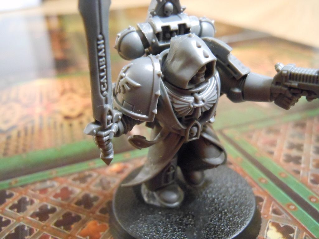 One of the space marine miniatures from the Deathwatch: Overkill board game, showing close up detailing of sculpting on the power sword.