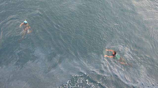 two guys diving for coins thrown from the ferry, Java to Bali