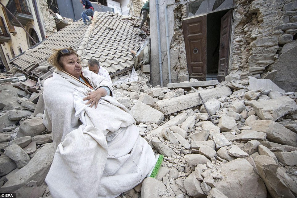 Huddled: A shocked woman and man are seen wrapped in blankets in front of collapsed houses in Amatrice, central Italy