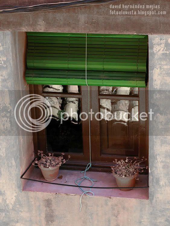 Dos macetascon plantas en el alféizar de una ventana de Albarracín, España