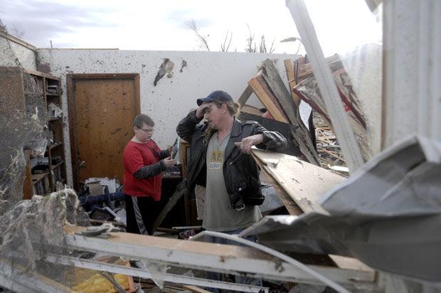 Gene Byrd e seu filho Devyn Byrd, de 14 anos, observam os estragos causados em casas de sua vizinhança em Harrisburg, Illinois (Foto: AP/Paul Newton/The Southern Illinoisan)