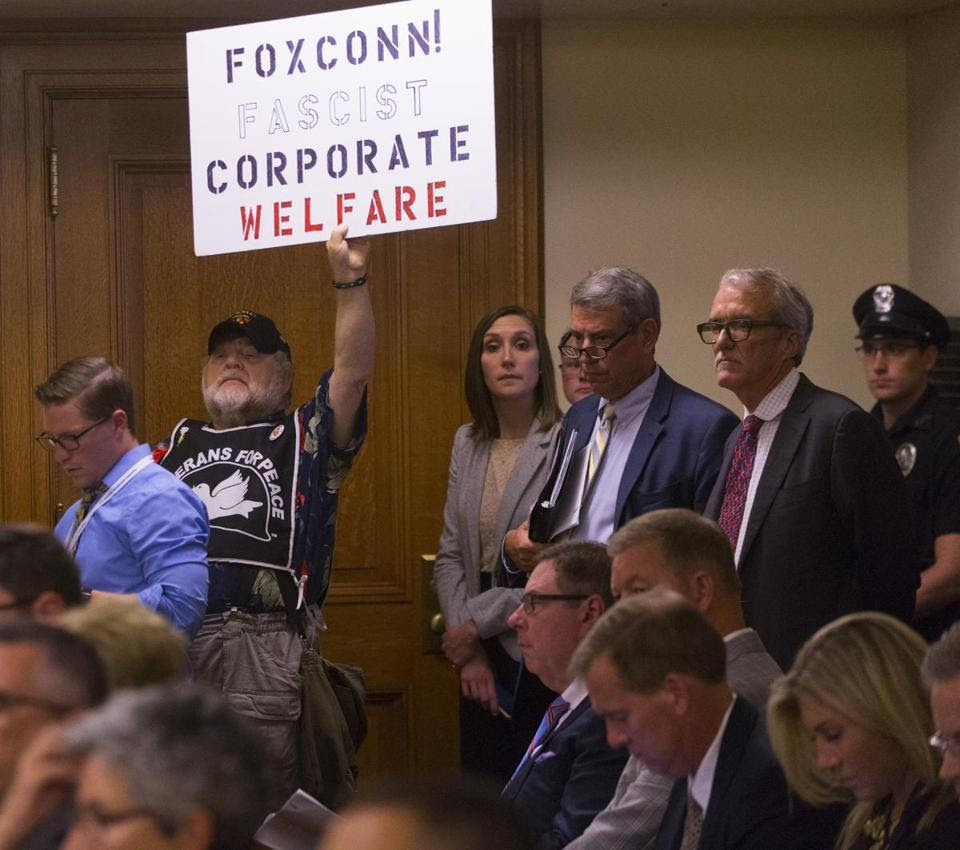 A lone protester held up a sign as the Assembly Committee on Jobs and Economy met about the incentive deal for Foxconn Thursday in Madison, Wis.