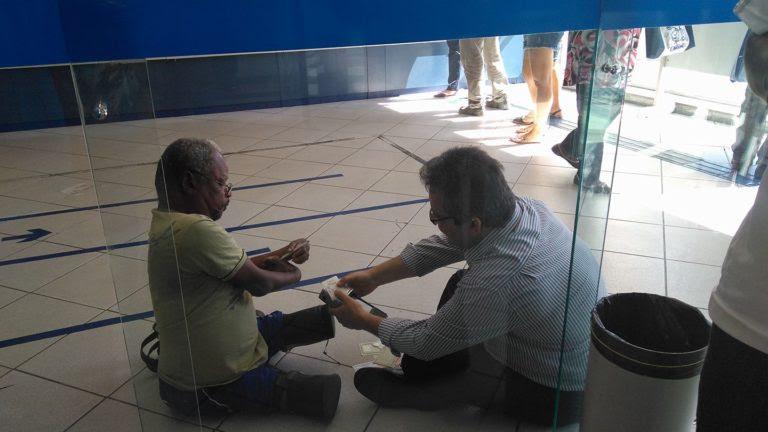 Gerente da Caixa senta no chão para atender cliente com deficiência e causa comoção na Internet