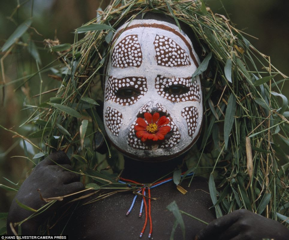 Intricate: This young child is shown with intricate face paint, a bright red flower in his mouth and strings of hand-strung beads