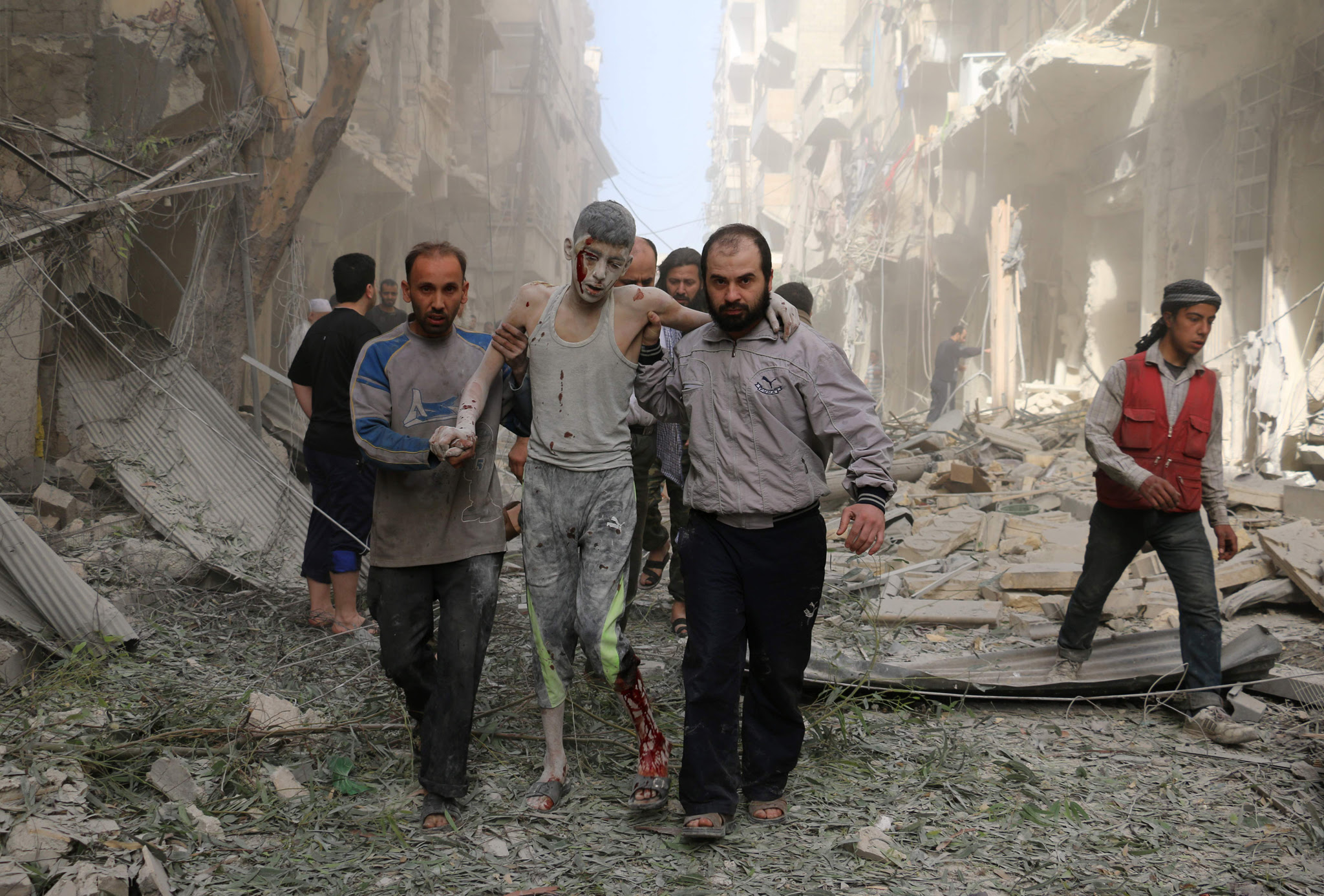 Syrians help a wounded youth following a...Syrians help a wounded youth following an air strike on the Fardous rebel held neighbourhood of the northern Syrian city of Aleppo on April 26, 2016.  / AFP PHOTO / AMEER ALHALBIAMEER ALHALBI/AFP/Getty Images