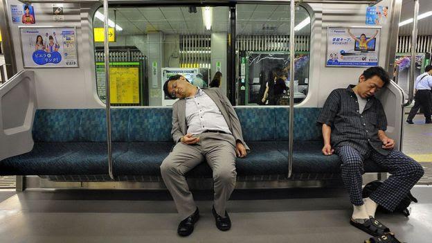 Dos pasajeros en Tokio toman una siesta en el metro.