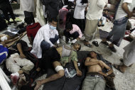 Wounded anti-government protestors lay on the ground as they received medical help at a field hospital during clashes with security forces in Sanaa, Yemen, Sunday, Sept. 18, 2011. Yemeni government forces opened fire with anti-aircraft guns and automatic weapons on tens of thousands of anti-government protesters in the capital pushing for ouster of longtime ruler Ali Abdullah Saleh, killing several people and wounding dozens. (AP Photo/Hani Mohammed)