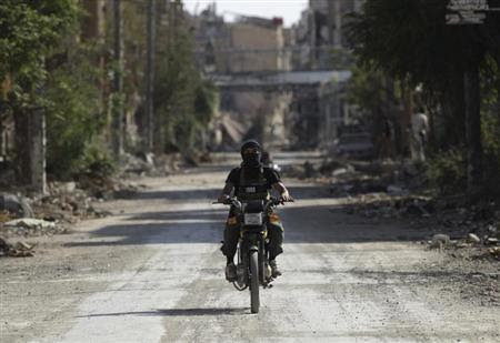 A fighter from the Islamist Syrian rebel group Jabhat al-Nusra rides a motorcycle along a deserted street in Deir al-Zor August 17, 2013. Picture taken August 17, 2013 file photo. REUTERS/Khalil Ashawi